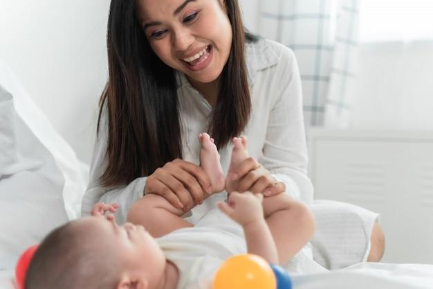 Jonge mooie aisan moeder met haar kleine schattige pasgeboren babymeisje thuis.