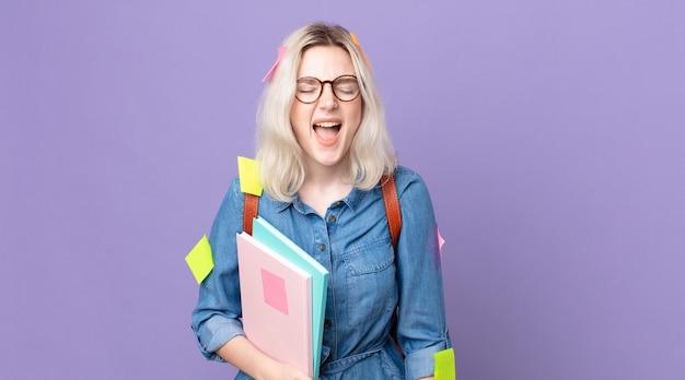 Jonge mooie albino-vrouw die agressief schreeuwt en er erg boos uitziet. studentenconcept