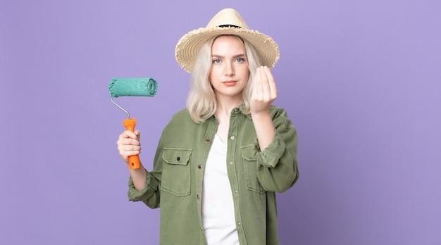 Jonge mooie albino-vrouw die capice of geldgebaar maakt, zegt dat je moet betalen en een verfroller vasthoudt