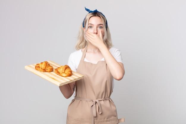 Jonge mooie albino-vrouw die de mond bedekt met handen met een schok met een dienblad met croissants
