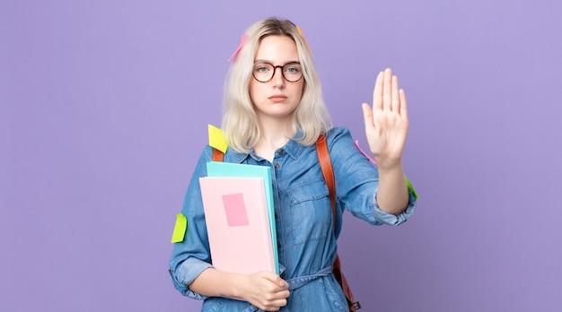 Jonge mooie albino-vrouw die er serieus uitziet en open palm toont die een stopgebaar maakt. studentenconcept