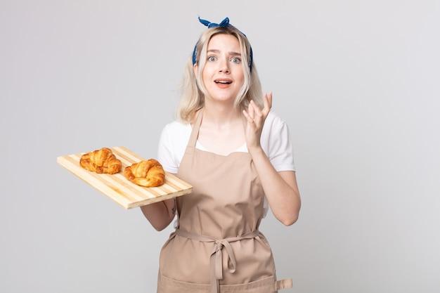 Jonge mooie albino-vrouw die er wanhopig, gefrustreerd en gestrest uitziet met een dienblad met croissants