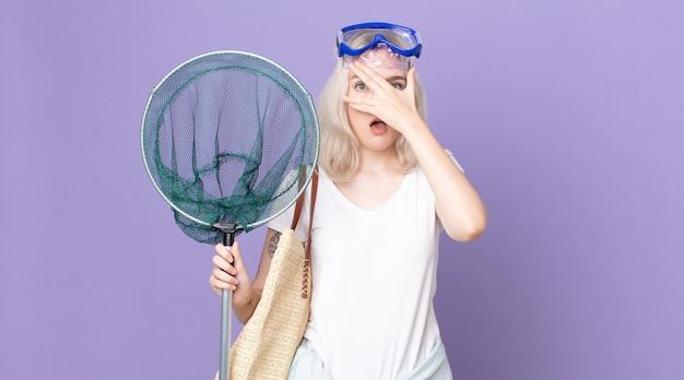 Jonge mooie albino-vrouw die geschokt, bang of doodsbang kijkt, haar gezicht bedekt met de hand met een bril en een visnet
