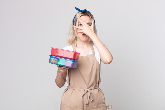 Jonge mooie albino-vrouw die geschokt, bang of doodsbang kijkt, haar gezicht bedekt met een hand die voedsel tupperwares vasthoudt
