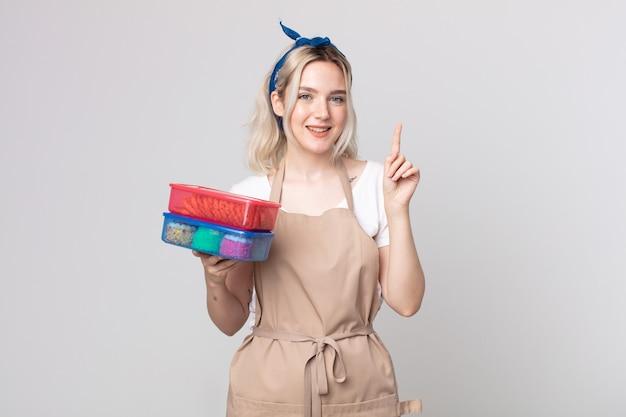 Jonge mooie albino-vrouw die lacht en er vriendelijk uitziet, met nummer één die voedsel tupperwares vasthoudt