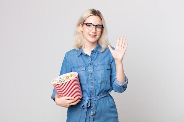Jonge mooie albino-vrouw die lacht en er vriendelijk uitziet, met nummer vijf met een emmer met popcorn
