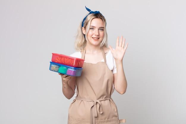 Jonge mooie albino-vrouw die lacht en er vriendelijk uitziet, met nummer vijf met voedsel tupperwares