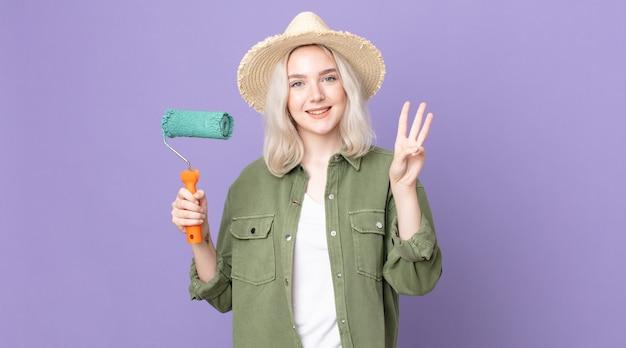 Jonge mooie albino-vrouw die lacht en er vriendelijk uitziet, nummer drie toont en een verfroller vasthoudt