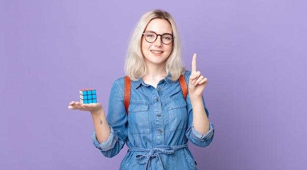 Jonge mooie albino-vrouw die lacht en er vriendelijk uitziet, nummer één laat zien en een intelligentiespel oplost