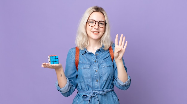 Jonge mooie albino-vrouw die lacht en er vriendelijk uitziet, nummer vier laat zien en een intelligentiespel oplost
