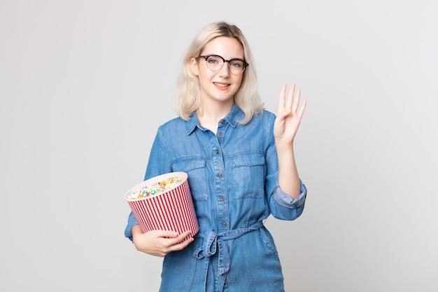 Jonge mooie albino-vrouw die lacht en er vriendelijk uitziet, nummer vier toont met een emmer met popcorn