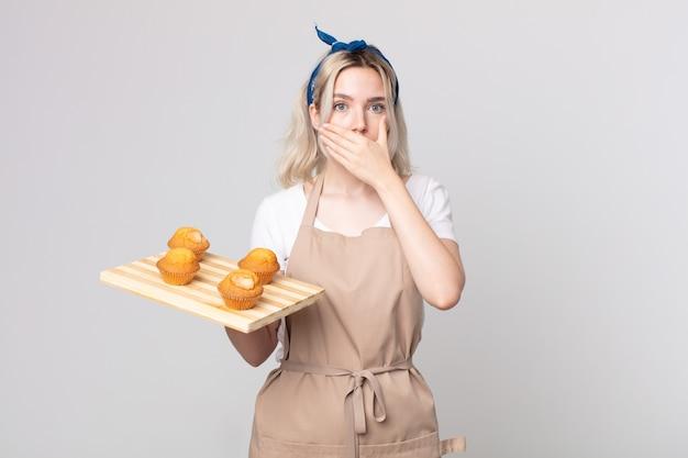 Jonge mooie albino-vrouw die mond bedekt met handen met een schok met een dienblad met muffins