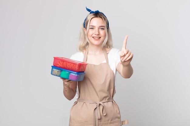 Jonge mooie albino-vrouw die trots en zelfverzekerd glimlacht en nummer één maakt met voedsel-tupperwares