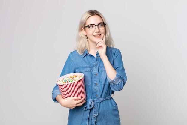 Jonge mooie albino-vrouw die vrolijk lacht en dagdroomt of twijfelt met een emmer met popcorn