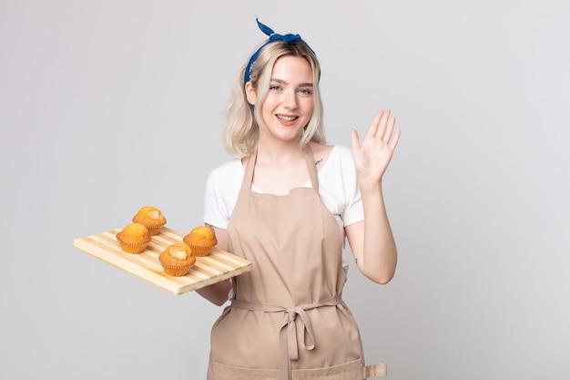 Jonge mooie albino-vrouw die vrolijk lacht, met de hand zwaait, je verwelkomt en begroet met een dienblad met muffins