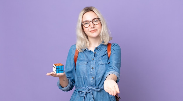 Jonge mooie albino-vrouw die vrolijk lacht met vriendelijk en een concept aanbiedt en toont en een intelligentiespel oplost