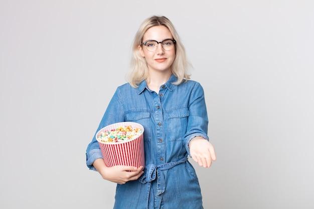 Jonge mooie albino-vrouw die vrolijk lacht met vriendelijk en een concept aanbiedt en toont met een emmer met popcorn