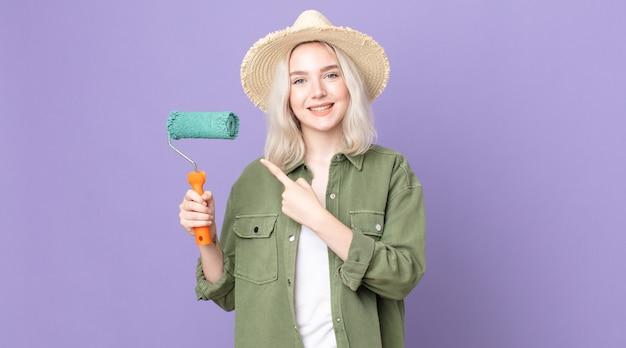 Jonge mooie albino-vrouw die vrolijk lacht, zich gelukkig voelt en naar de zijkant wijst en een verfroller vasthoudt