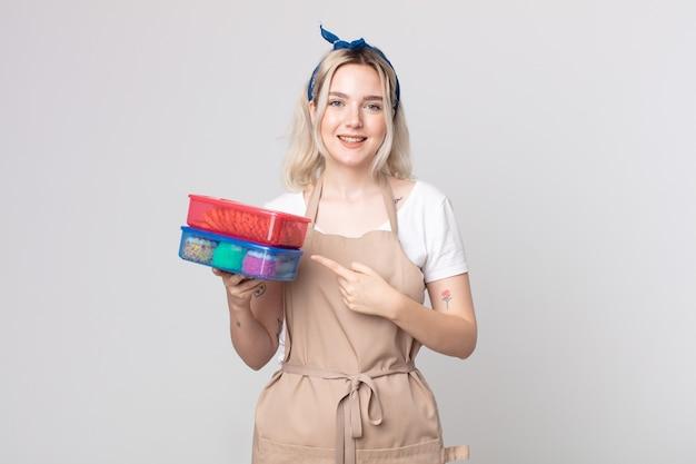 Jonge mooie albino-vrouw die vrolijk lacht, zich gelukkig voelt en naar de zijkant wijst met voedsel tupperwares