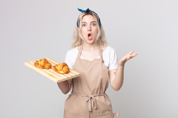 Jonge mooie albino-vrouw die zich extreem geschokt en verrast voelt met een dienblad met croissants
