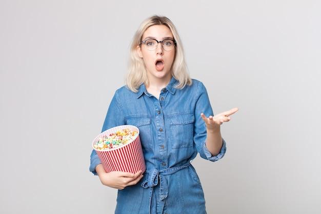 Jonge mooie albino-vrouw die zich extreem geschokt en verrast voelt met een emmer met popcorn