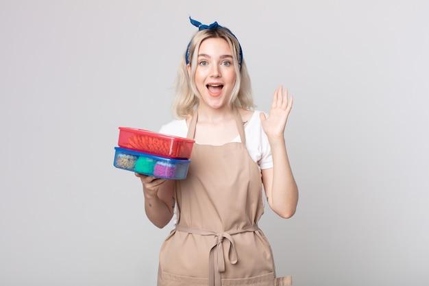Jonge mooie albino-vrouw die zich gelukkig en verbaasd voelt over iets ongelooflijks met voedsel tupperwares