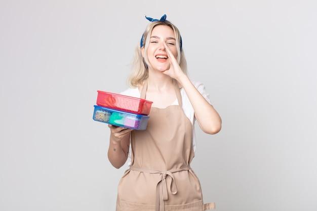 Jonge mooie albino-vrouw die zich gelukkig voelt, een grote schreeuw geeft met de handen naast de mond met voedsel tupperwares