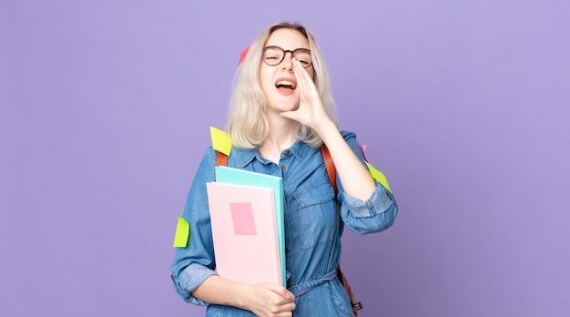 Jonge mooie albino-vrouw die zich gelukkig voelt, een grote schreeuw geeft met de handen naast de mond. studentenconcept