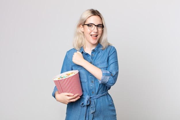 Jonge mooie albino-vrouw die zich gelukkig voelt en een uitdaging aangaat of viert met een emmer met popcorn