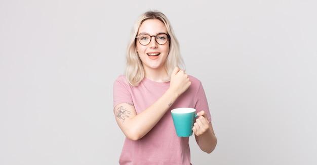 Jonge mooie albino-vrouw die zich gelukkig voelt en een uitdaging aangaat of viert met een koffiemok