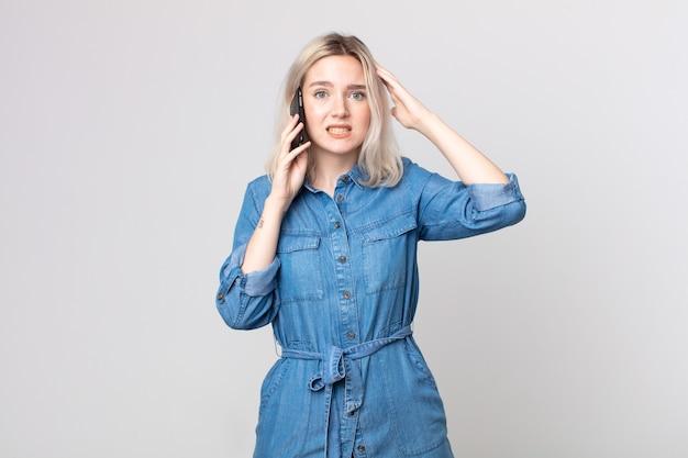 Jonge mooie albino-vrouw die zich gestrest, angstig of bang voelt, met de handen op het hoofd en praat met een smartphone