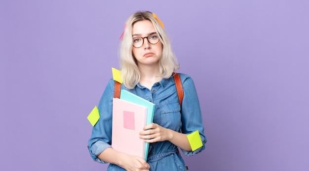 Jonge mooie albino-vrouw die zich verdrietig en zeurt met een ongelukkige blik en huilt. studentenconcept