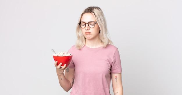 Jonge mooie albino-vrouw die zich verdrietig, overstuur of boos voelt en opzij kijkt met een ontbijtkom