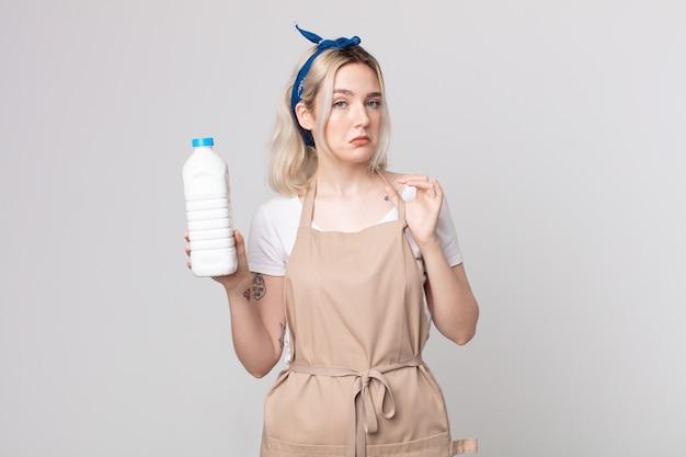 Jonge mooie albinovrouw die er arrogant, succesvol, positief en trots uitziet met een fles melk