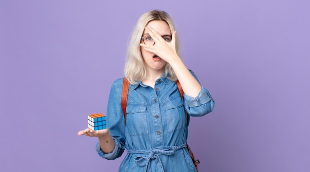 Jonge mooie albinovrouw die geschokt, bang of doodsbang kijkt, haar gezicht bedekt met de hand en een intelligentiespel oplost