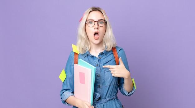 Jonge mooie albinovrouw die geschokt en verrast kijkt met wijd open mond, wijzend naar zichzelf. studentenconcept