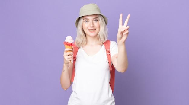 Jonge mooie albinovrouw die lacht en er gelukkig uitziet, gebarend overwinning of vrede .zomerconcept