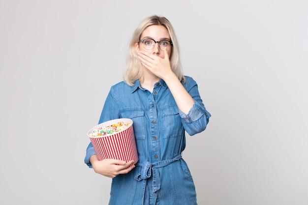 Jonge mooie albinovrouw die mond bedekt met handen met een schok met een emmer met popcorn