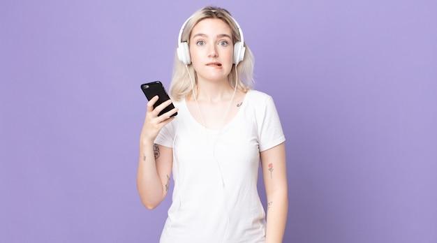 Jonge mooie albinovrouw die verbaasd en verward kijkt met koptelefoon en smartphone
