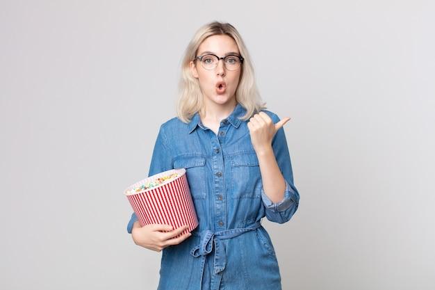 Jonge mooie albinovrouw die verbaasd in ongeloof kijkt met een emmer met popcorn