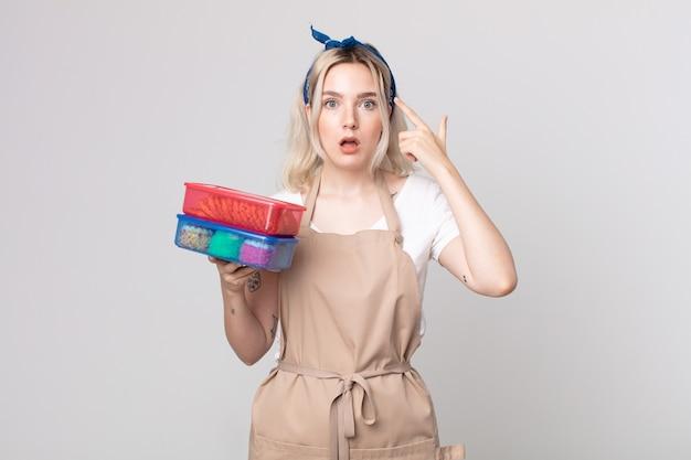Jonge mooie albinovrouw die verrast kijkt, een nieuwe gedachte, idee of concept realiseert met voedsel tupperwares