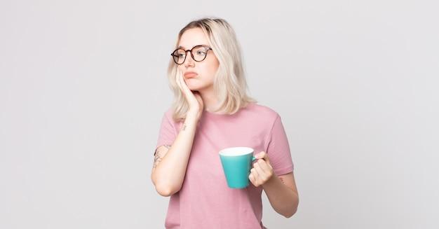 Jonge mooie albinovrouw die zich verveeld, gefrustreerd en slaperig voelt na een vermoeiende met een koffiemok