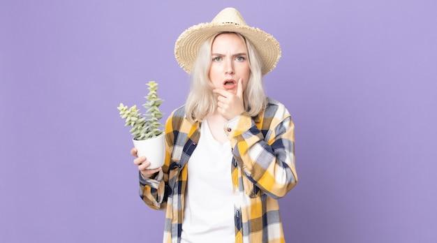 Jonge mooie albinovrouw met wijd open mond en ogen en hand op kin en houdt een kamerplantcactus vast