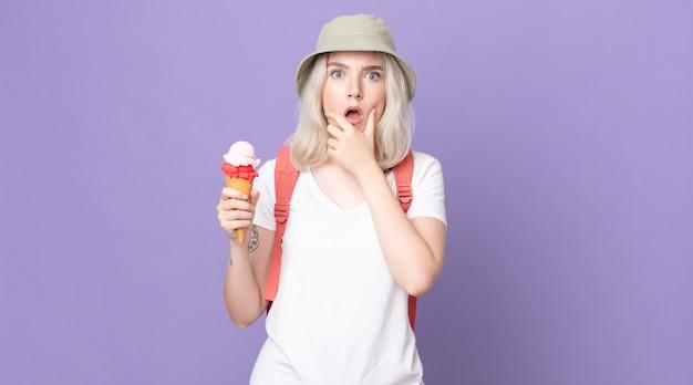 Jonge mooie albinovrouw met wijd open mond en ogen en hand op kin .summer concept
