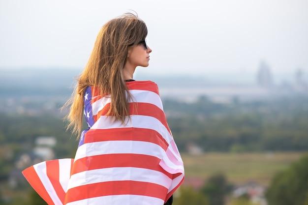 Jonge mooie amerikaanse vrouw met lang haar die op de windvlag van de v.s. zwaait