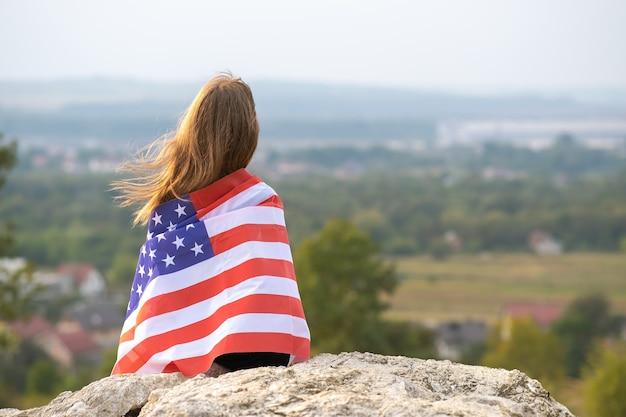 Jonge mooie amerikaanse vrouw met lang haar die zwaait op de vlag van de v.s. van de wind op haar schouders die buiten rusten en genieten van een warme zomerdag.
