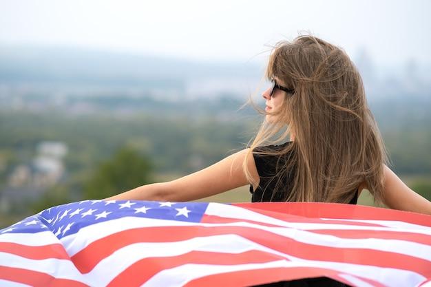 Jonge mooie amerikaanse vrouw met lang haar die zwaait op de vlag van de v.s. van de wind op haar schouders die buiten staat en geniet van een warme zomerdag.