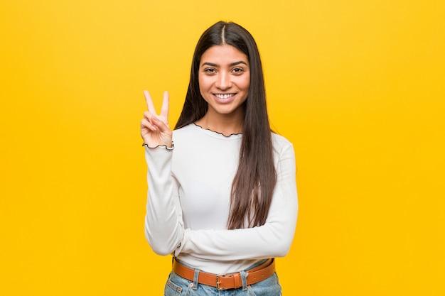 Jonge mooie arabische vrouw die nummer twee met vingers toont.