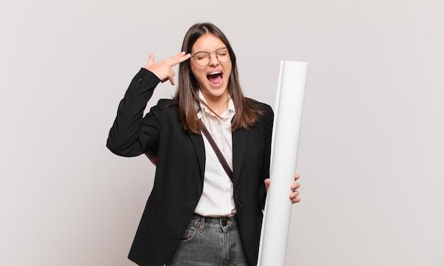 Jonge mooie architectenvrouw die ongelukkig en gestrest kijkt, zelfmoordgebaar maakt een pistoolteken met de hand, wijzend naar het hoofd