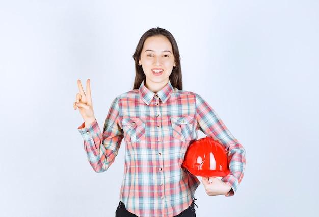 Jonge mooie architectenvrouw die veiligheidshelm houdt en overwinningsteken toont.